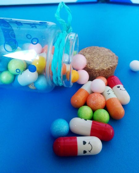 Close-up of multi colored pills on blue table