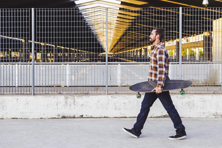 Full length of man standing on skateboard in city