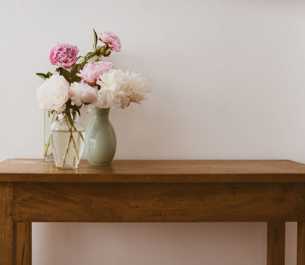 Pink and white peonies in glass and ceramic vases on oak wooden table against neutral wall - warm matte filter effect and selective focus Background Beauty Ceramic Closeup Copy Space Cream Decoration Delicate Effect Filter Floral Flowers Fragile Glass Green Indoors  Interiors Matte Natural Nature Neutral Oak Peonies Petals Pink Retor Rustic Shelf Side Table Spring Table Vases Vintage Wall Warm White Wooden Fragility Vulnerability  Wood - Material Still Life Freshness Beauty In Nature No People Close-up Flower Head Arrangement Bunch Of Flowers Container