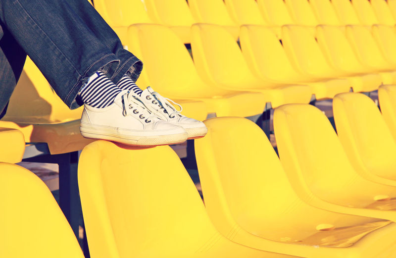 Low Section Of Person Wearing Shoes Sitting On Chair In Stadium