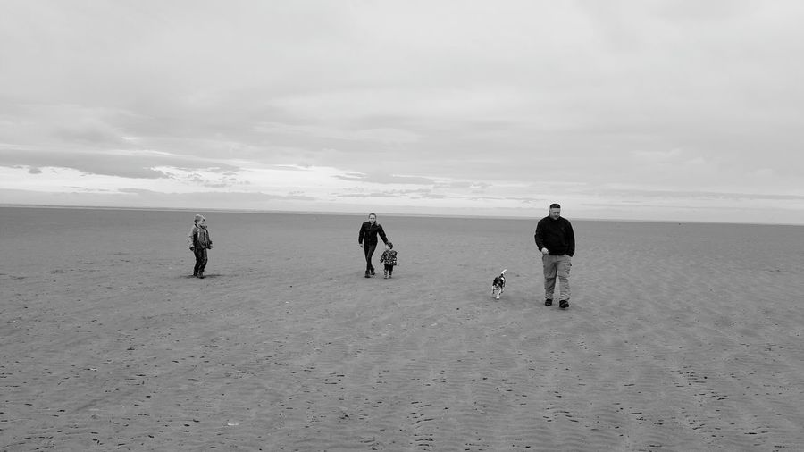 Full length of family with dog at beach