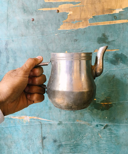 Cropped Image Of Tea Pot Against Wooden Wall