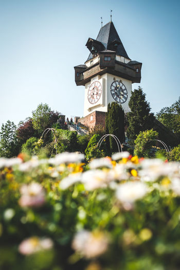 Clock Tower in Graz (Grazer Uhrturm) Austria City Graz Steiermark Architecture Blue Clear Sky Clock Clock Tower Day Flower Flowers Focus On Background Low Angle View Nature No People Outdoors Schlossberg Sky Spring Springtime Summer Tower Travel Destinations Uhrturm
