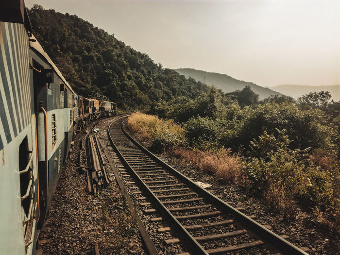 Railroad tracks by mountain against sky