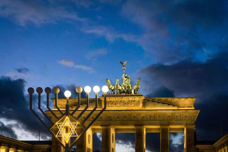 Low angle view of illuminated brandenburg gate against blue sky