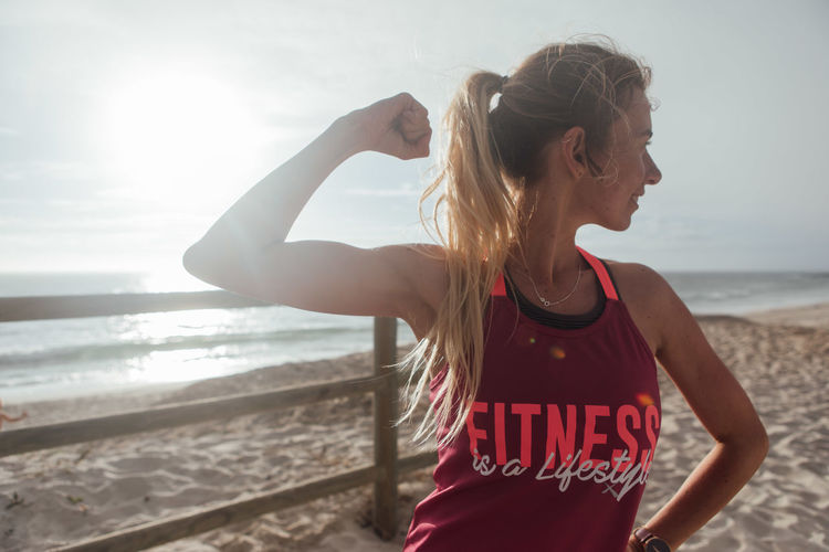 Woman Flexing Muscle At Beach Against Sky