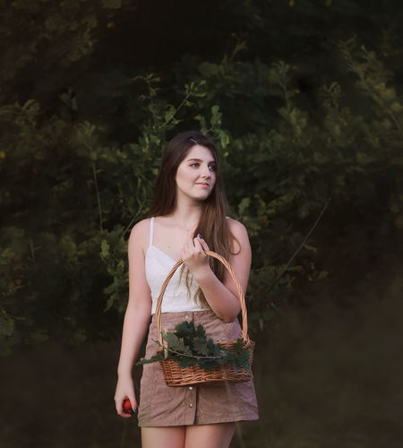 Woman holding basket while standing against trees