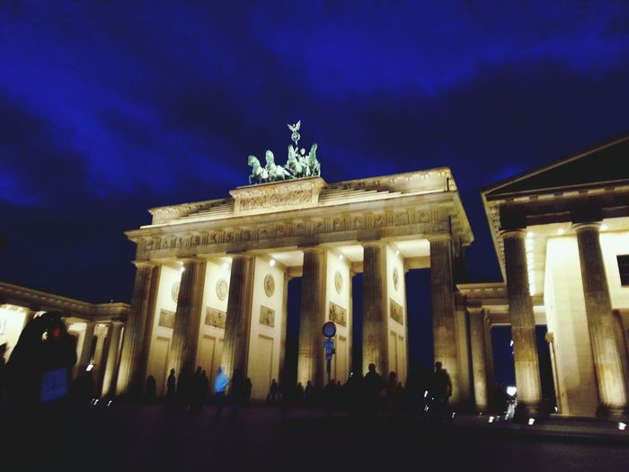 Low angle view of brandenburg gate against cloudy sky