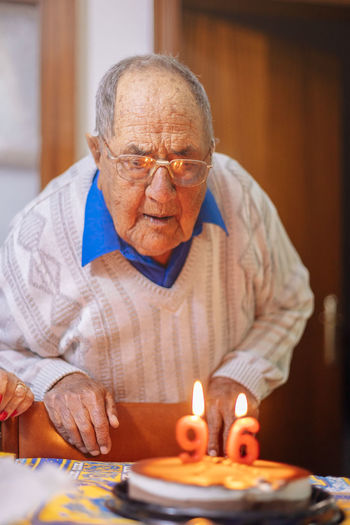 Senior Adult Senior Men Burning One Person Adult Indoors  Fire Men Front View Table Waist Up Males  Sitting Lifestyles Candle Eyeglasses  Flame Retirement Birthday Candles