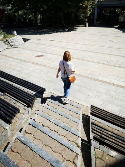 Rear view of woman walking on steps in city