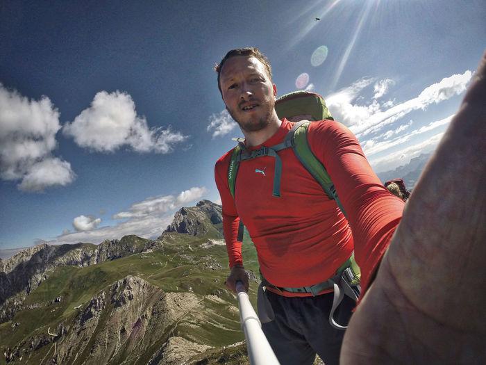 Portrait of hiker holding selfie stick on mountain against sky