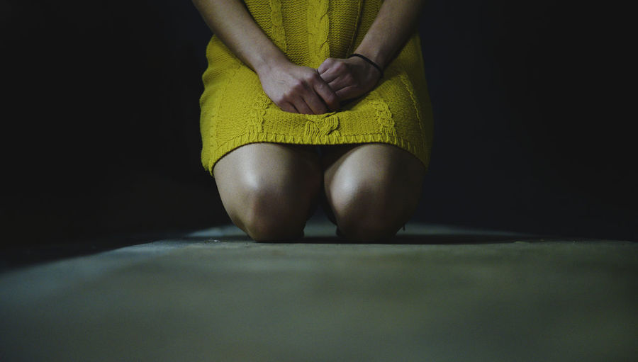 Midsection Of Woman Praying While Kneeling On Floor