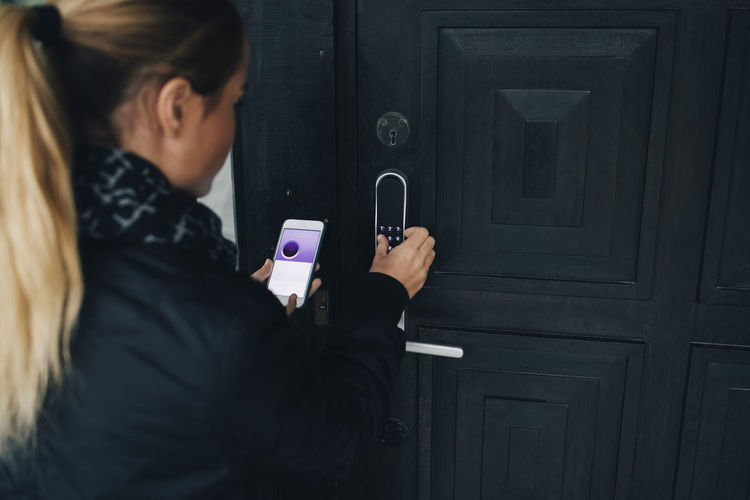 Midsection of woman using smart phone on door