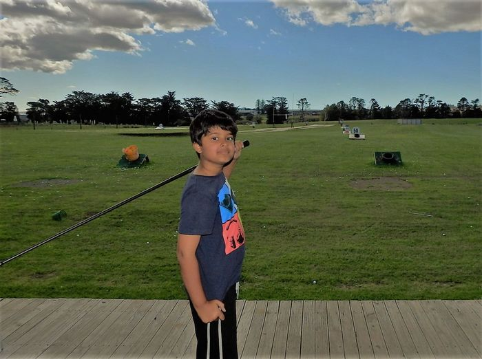 Boy poses after taking a driving golf shot at the driving range Boy Posing Casual Clothing Driving Range Golf Club Golfing With Babes Golfing With Kids Grassy Green Color Kids Golf Landscape Leisure Activity Lifestyles Outdoors Portrait Sky Sunlight The Portraitist - 2016 EyeEm Awards The Portraitist - 2017 EyeEm Awards