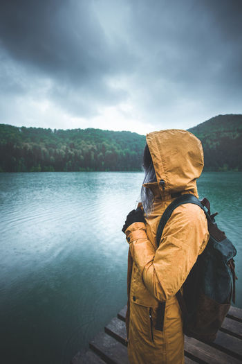 Young woman wearing raincoat while standing on pier by lake during rainy season