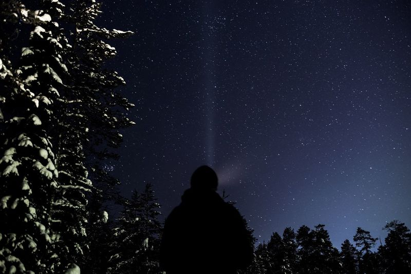 Silhouette Man With Flashlight Against Constellation