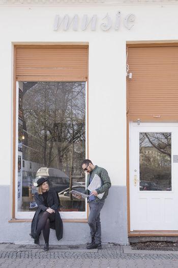 Man sitting on window of building