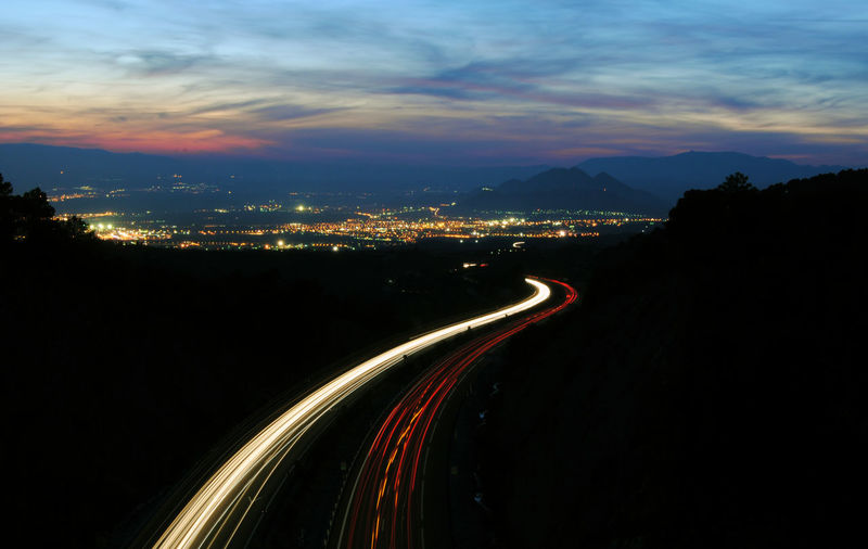 Light Trails On Road By Silhouette Mountain Against Sky At Night