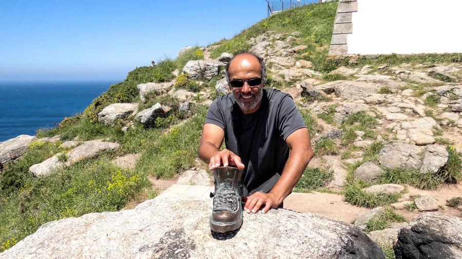 Man Keeping Boot On Rock At Mountain