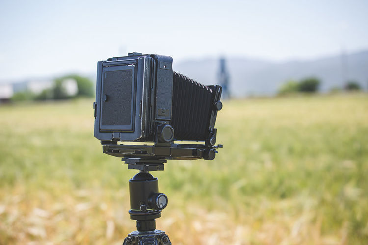 Close-up of camera on field against sky