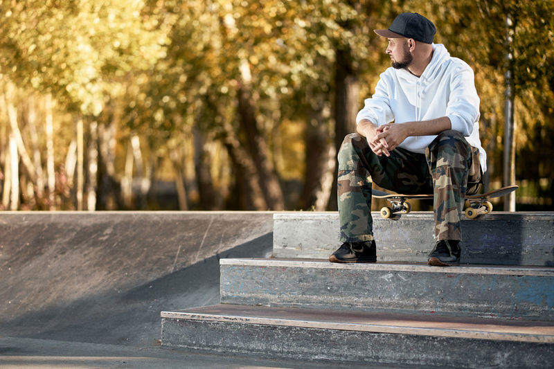 Man sitting with skateboard on staircase at park