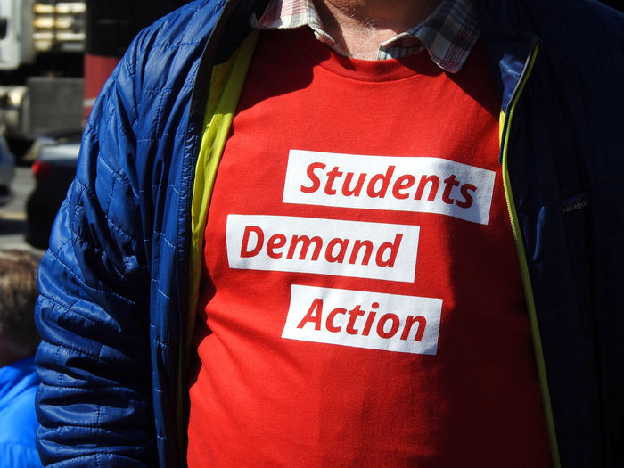 "A ""Students Demand Action"" t-shirt at the pro- gun control March For Our Lives in Washington, DC on March 24, 2018. Protest Activism Adult Adults Only Casual Clothing Close-up Clothing Day Gun Control Gun Safety Indoors  Jacket March For Our Lives Mass Shooting Midsection One Person One Woman Only People Real People Red Reflective Clothing Standing Text Uniform Women"