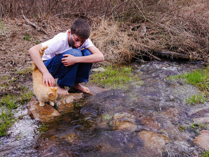 Teenage Boy With Cat Crouching By Stream In Forest