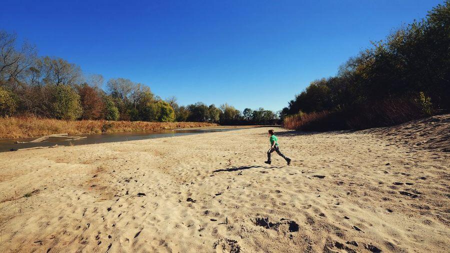 Boy Running On Sand At Little Blue River Against Sky