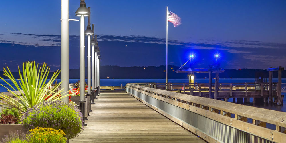 Illuminated pier by sea against blue sky at night