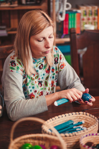 Woman decorating eater eggs while sitting by table