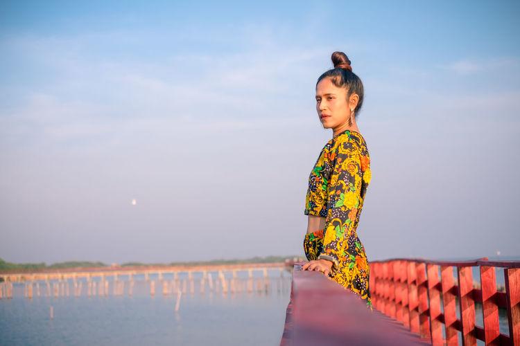 Woman standing on footbridge over sea against sky