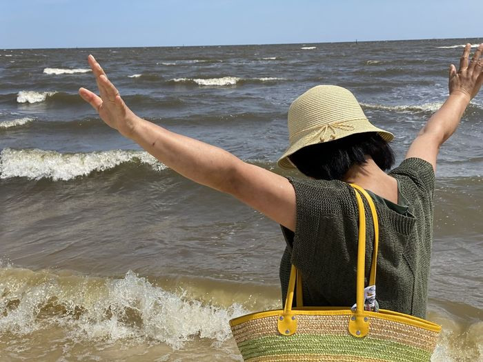 Rear view of woman with arms raised at beach against sky