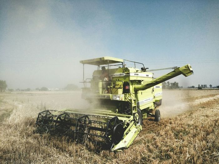 View Of Agricultural Vehicle At Work In Field