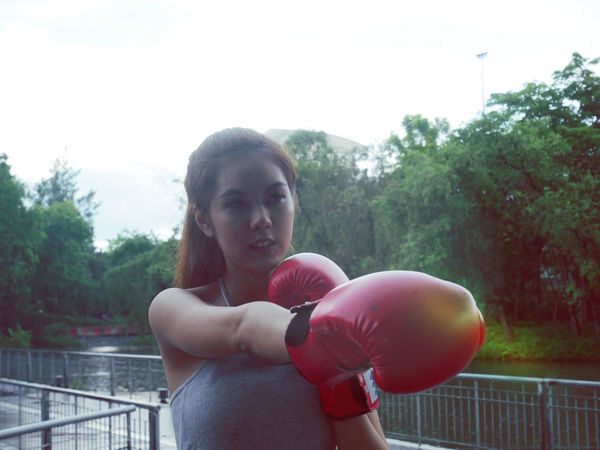 Beautiful Asia girl boxing. Boxing - Sport Boxing Glove Day Focus On Foreground Front View Hairstyle Leisure Activity Lifestyles Looking Looking At Camera Nature One Person Portrait Real People Sport Standing Tree Young Adult Young Women