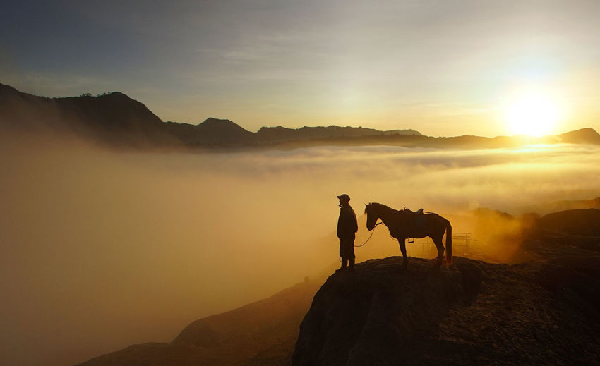 Silhouette man and horse on mountain cliff