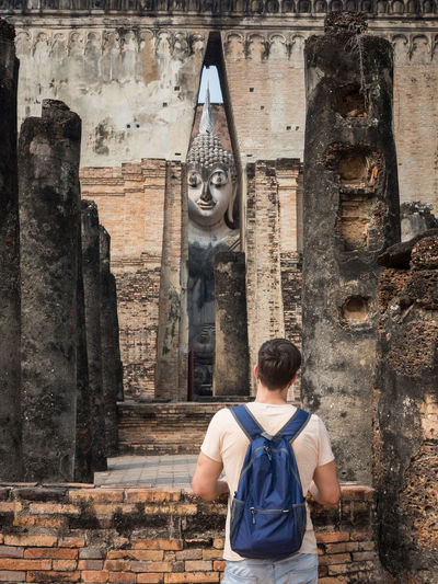 Rear view of man standing outside temple against building