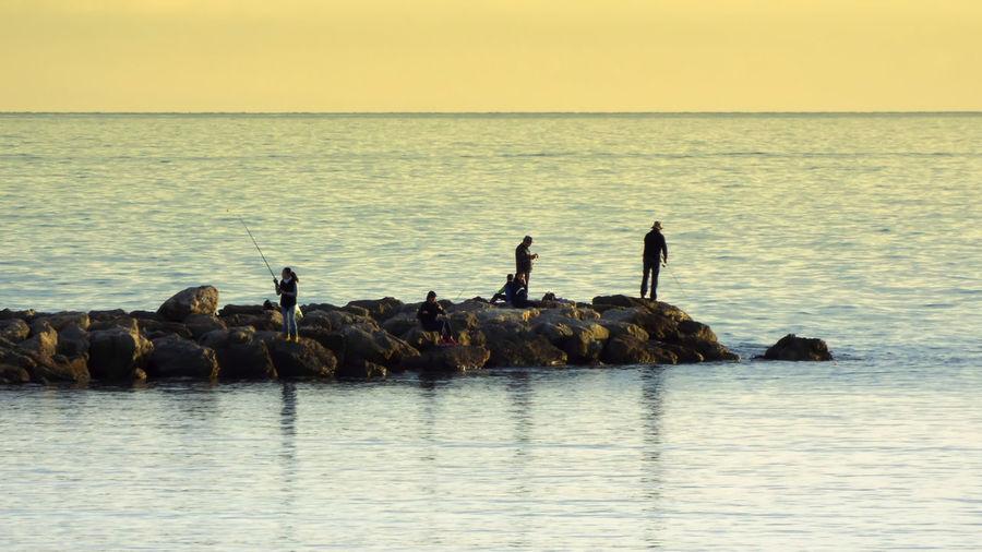 Wide shot of people fishing in sea