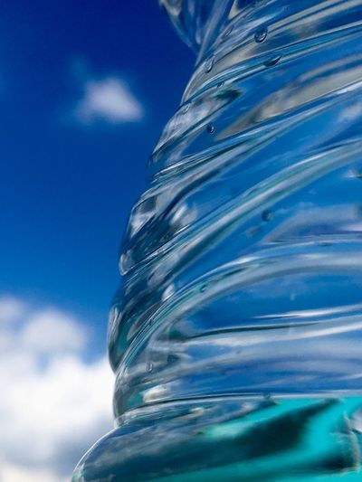 Low angle view of water bottle against blue sky
