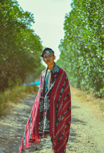 Portrait of young man standing with shawl on dirt road