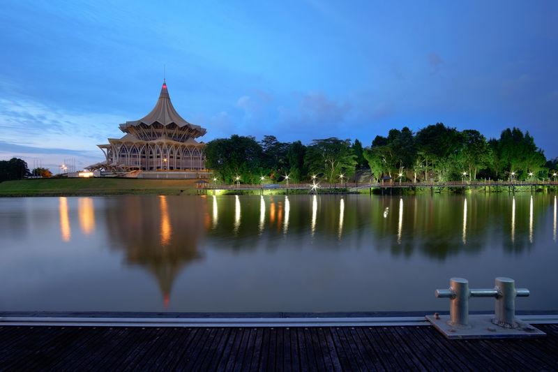 Sarawak state legislative assembly by river against blue sky