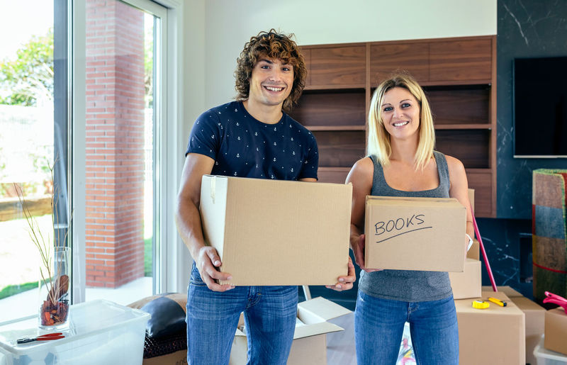 Couple carrying moving boxes in their new home Box Cardboard Box Couple Family Happy Horizontal Man Moving New Unpacking Woman Apartment Cardboard Caucasian Enjoy Female Holding House Lifestyles Male Mortgage Packed Real People Relocation Smiling