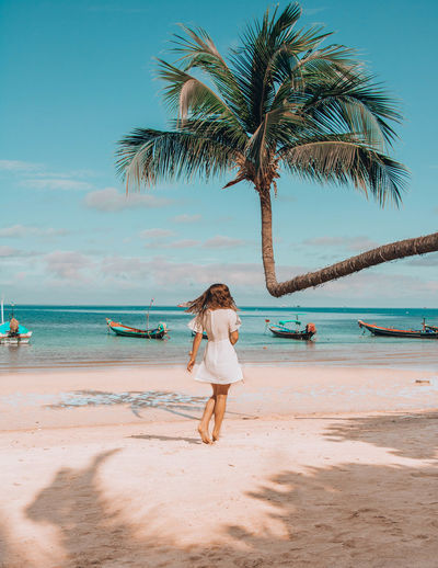 Full length of woman standing by palm tree on beach against sky