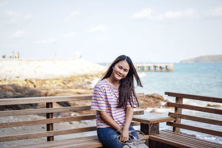 Portrait of smiling young woman sitting on bench by sea