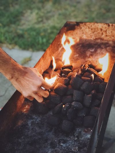 Close-up of hand by burning coals on barbeque grill