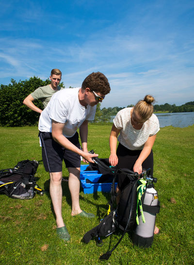 People preparing for scuba diving on grassy field against sky