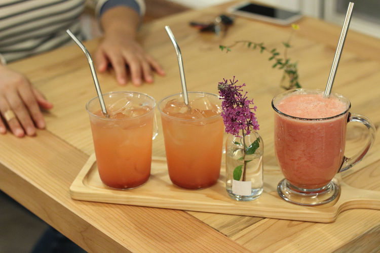 High angle view of fresh drinks with flower vase in serving board on wooden table