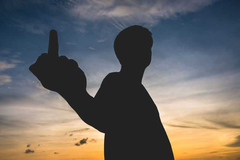 Silhouette man showing obscene gesture against sky during sunset