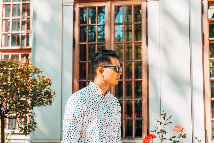Young man wearing sunglasses while standing against window