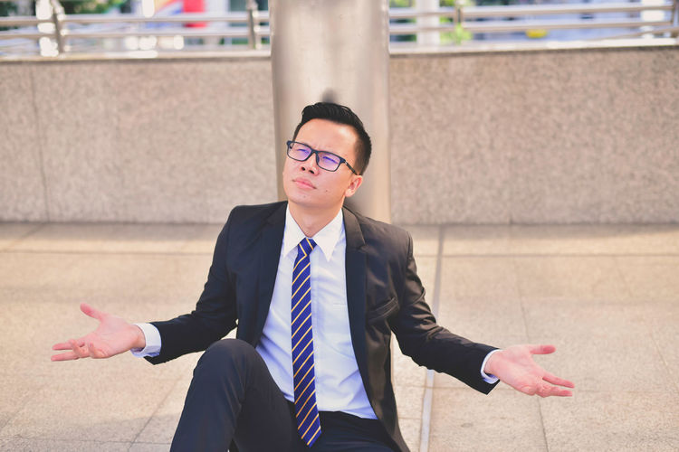 Stressed businessman sitting in city