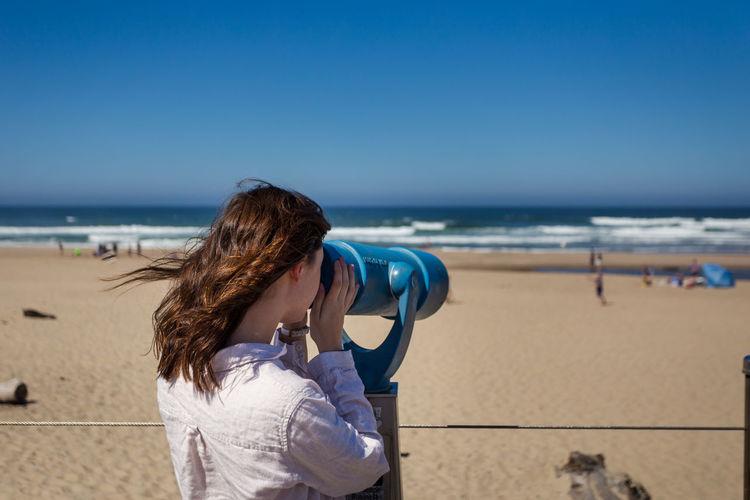 Woman looking through telescope at beach against clear blue sky